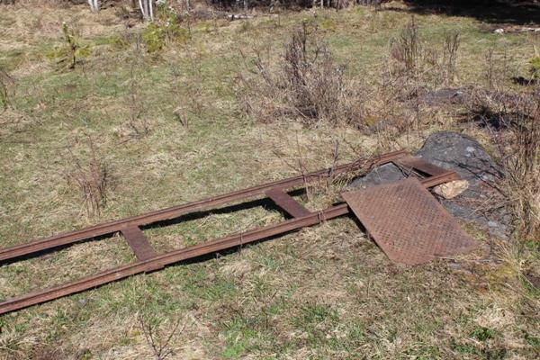 Звено рельсов экстра узкой колеи. К рельсам приклепаны стальные шпалы. Рядом решетка с бутары